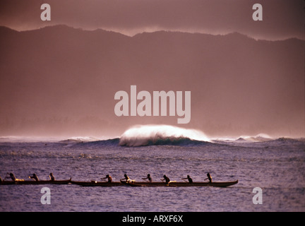 A canoe clug paddles into the shore at Haleiwa on the north shore of Oahu - Stock Photo