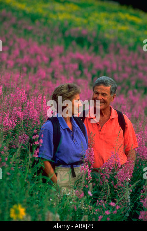 Portrait of senior couple hiking in a field of purple flowers in the mountains - Stock Photo