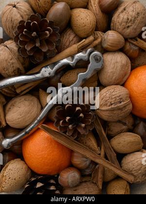 Mixed nuts satsumas cinnamon sticks and nut crackers - Stock Photo