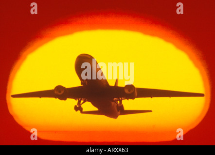 computer graphic silhouette airplane commercial jet aitcraft enlarged sun - Stock Photo