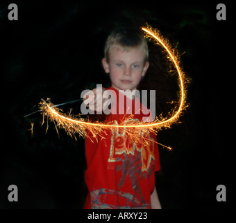 Boy Using A Firework Sparkler To Paint With Light - Stock Photo