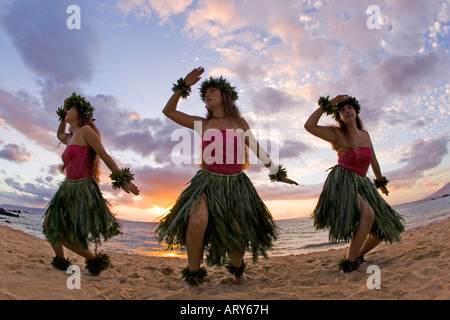 Three hula dancers in ti leaf skirts dance on the beach at sunset at Makena, Maui. - Stock Photo