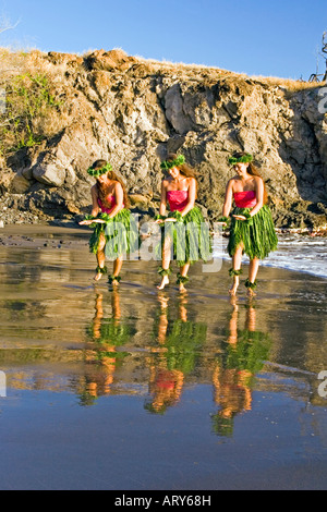 Three hula dancers in ti leaf skirts dance at the water's edge with their reflection at Olowalu, Maui. - Stock Photo