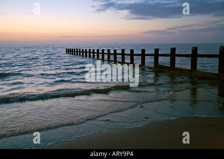 Beach and breakwater at dusk with wind farm on horizon Rhyl North Wales UK - Stock Photo