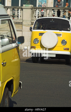 Two yellow Volkswagen VW camper vans facing each other across the road as if in conversation - Stock Photo