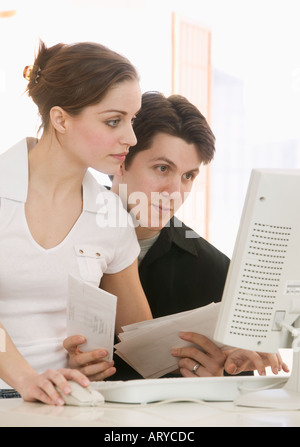 Young couple working at computer - Stock Photo