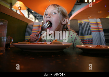 girl eating pancakes in a restaurant - Stock Photo