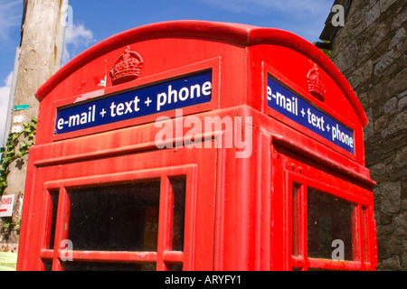 Traditional red telephone box offering email and texting services for the local community in rural  village - Stock Photo