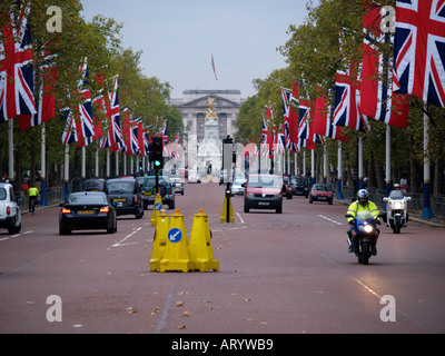 The Mall with traffic and flags looking towards Queen Victoria memorial London UK - Stock Photo