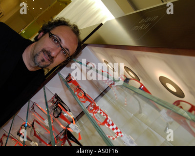 Alain Mikli French spectacle frame designer in front of a display case of his frames - Stock Photo