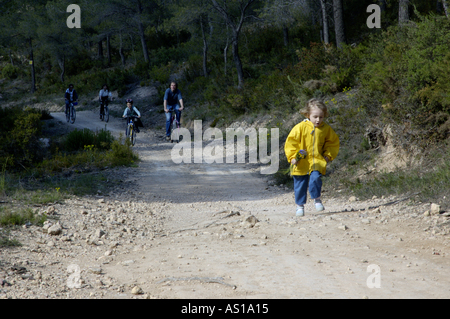 Girl running ahead of her family on a dirt road while they cycle behind, Vitrolles, Provence, France. - Stock Photo