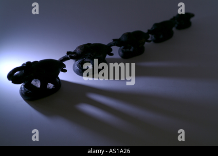 Statues of an elephant family attached each others with their trunks - Stock Photo