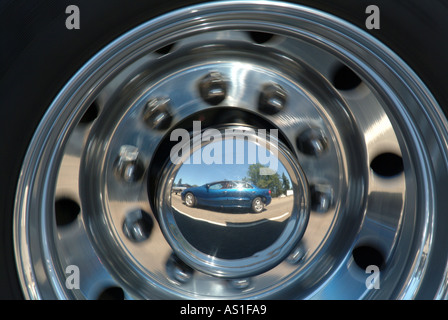 reflection of car in wheel of truck stock photo
