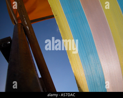 Sun shining through a deck chair's striped colourful fabric in early morning sunrise on Shanklin Beach, Shanklin, - Stock Photo