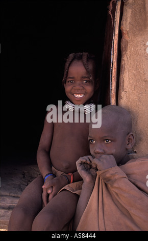 Himba boy and girl photographed at the entrance to the granary hut Kaokoveld tribal areas North west of Opuwo Namibia - Stock Photo