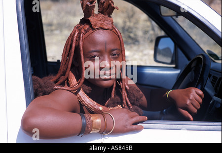 Himba woman Distinctive hair decoration and adornments At the wheel of a 4x4 Kaokoveld S of Opuwo Namibia - Stock Photo