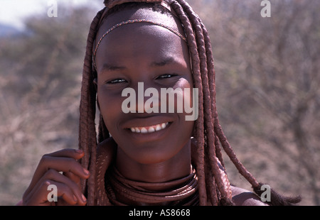 Young friendly Himba woman and her distinctive hair decoration and adornments Kaokoveld south of Opuwo Namibia - Stock Photo