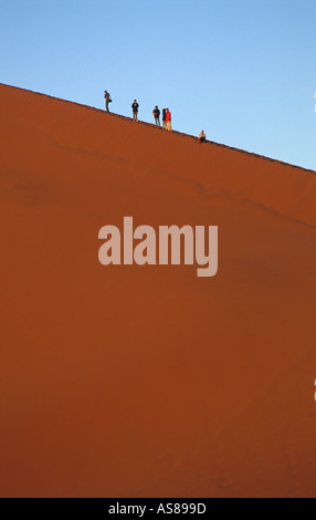 Early morning sun lights Dune 45 travellers climb to the summit Namib Naukluft National Park Namibia - Stock Photo