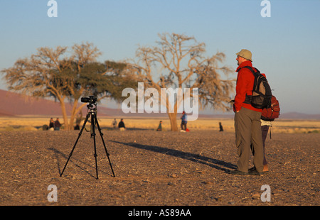 Photographer with tripod photographing Dune 45 at first light Namib Naukluft National Park Namibia - Stock Photo