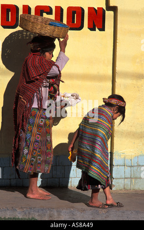 Mother stops as her child pauses to slip her shoe on Walking from market Zunil Guatemala - Stock Photo