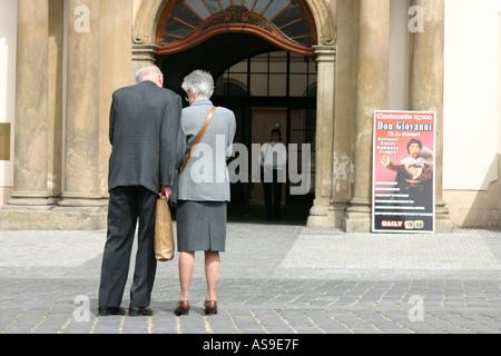 Old Couple Outside Doorway - Stock Photo