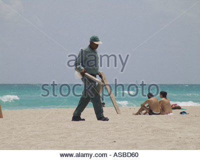 Worker taking some washed on wood from the beach Miami USA - Stock Photo