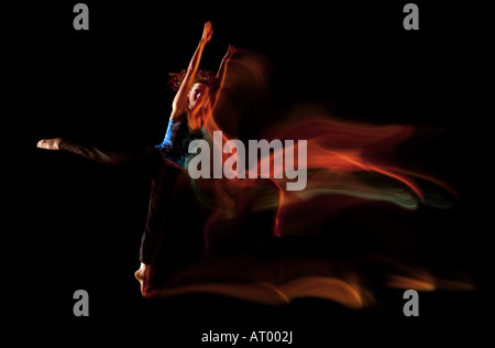light-trail lighttrail dancer female blackbackground jump jumping leaping through darkness ghostly shadows movment - Stock Photo