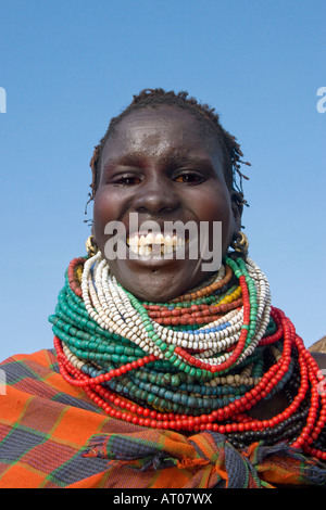 Laughing Women of the Nyantatom Tribe Displays Her Piles of Beads, Omo River Valley, Ethiopia - Stock Photo