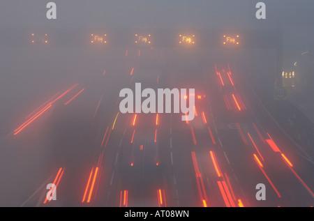 Lights streak Northwards during dawn fog makes car driving hazardous on M25 motorway at crossing of Dartford Bridge - Stock Photo