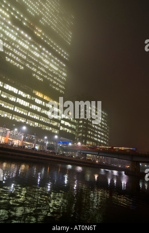 Vertical wide angle of a Docklands Light Railway train DLR leaving Heron Quays station in Canary Wharf on a foggy - Stock Photo