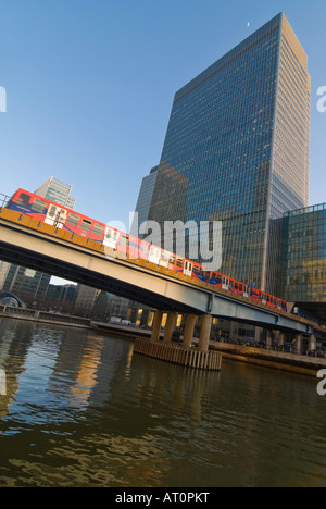 Vertical wide angle of a Docklands Light Railway train [DLR] leaving Heron Quays station on a bright sunny day. - Stock Photo