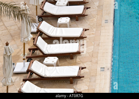 Horizontal elevated close up of a row of empty clean white sunbeds arranged around the poolside of a 5 star rated - Stock Photo