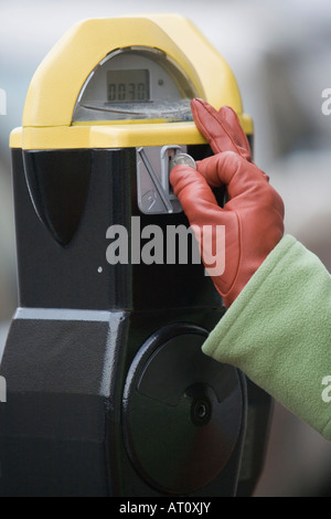 Close-up of a person's hand inserting a coin into a parking meter - Stock Photo