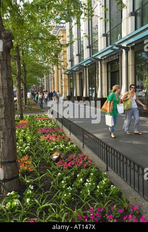 ILLINOIS Chicago Two women shoppers walking down Michigan Avenue sidewalk spring flowers - Stock Photo
