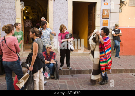 MEXICO Guanajuato Mexican man showing blankets serapes and rugs to tourists in street - Stock Photo
