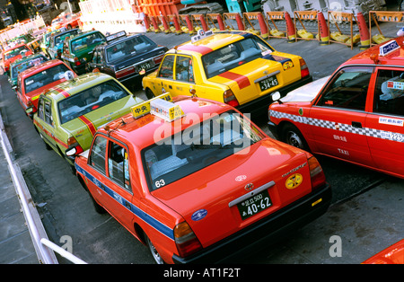 Taxis (Toyota Comfort) queue for passengers outside Shibuya station in central Tokyo - Stock Photo