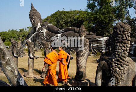 Novices in front of the Reclining Buddha at Xieng Khuan (Buddha Park) near Vientiane, Laos - Stock Photo