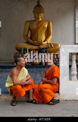 Novices in front of a Buddha at Wat Sok Pa Luang, Vientiane, Laos - Stock Photo