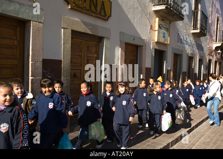 MEXICO Guanajuato Large group of young students in school uniforms walking down sidewalk holding hands - Stock Photo
