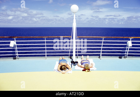 Two women sunbathing on the deck of a cruise ship - Stock Photo