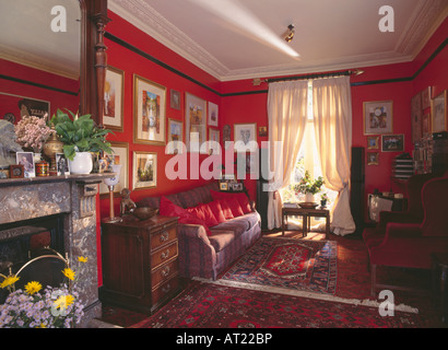 Cream curtains in red livingroom with patterned carpet and pictures above the sofa - Stock Photo