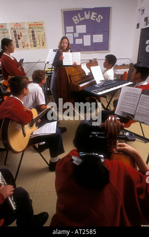 SCHOOL MUSIC GROUP BAND CLASS TEACHER Multicultural group of teenage students playing various instruments in music - Stock Photo