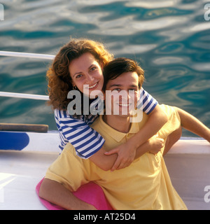 Smiling young couple on a boat in perfect late afternoon sunshine with sea background - Stock Photo