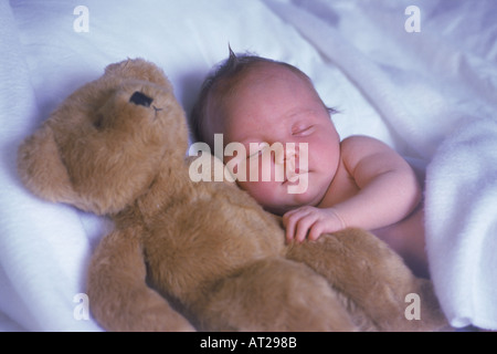 Baby sleeping with best teddy bear buddy on a bed of white sheets like a cloud - Stock Photo