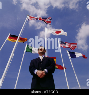 A business man surrounded by flags from various countries - Stock Photo