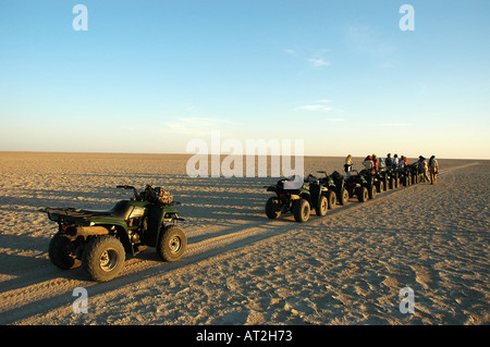 Row of quad bikes lined up across the Makgadikgadi salt pans near Jacks camp in Botswana southern Africa Stock Photo