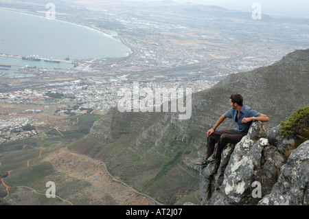 Solitary man looking over cape town from summit of Table Mountain South Africa - Stock Photo