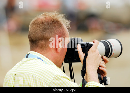 a man photographer using a digital slr camera with a lon telephoto zoom lens attached taking a photograph picture - Stock Photo