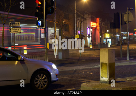 car waiting at traffic lights at shaftesbury square in belfast city centre on a quiet city night in the uk - Stock Photo