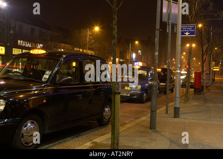 taxis and cabs waiting on street cab rank for passengers in pub and club nightlife area in bradbury place belfast - Stock Photo